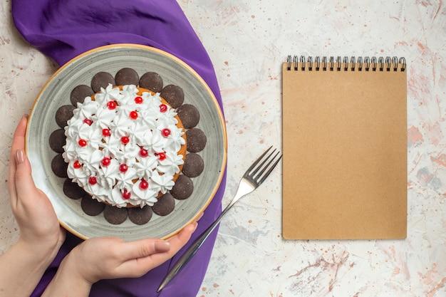 Vista superior do bolo com creme de confeitaria no prato no caderno de garfo xale roxo de mão feminina