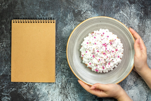 Vista superior do bolo com creme de confeiteiro branco em bandeja redonda cinza no caderno de mão feminina na mesa cinza