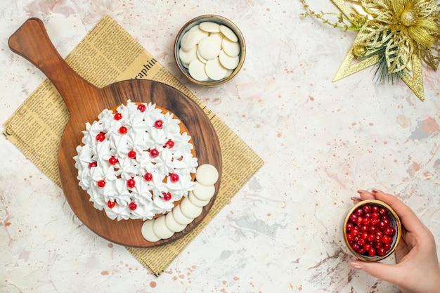 Vista superior do bolo com creme de confeiteiro branco na placa de madeira no jornal e enfeite de natal