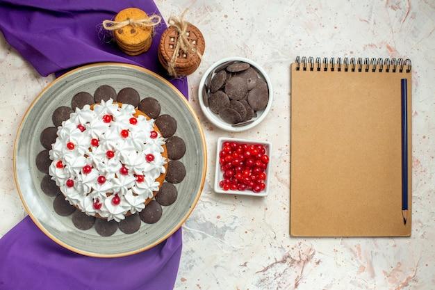 Vista superior do bolo com creme de confeiteiro em prato oval xale roxo biscoitos amarrados com corda de chocolate e frutas em lápis de tigelas