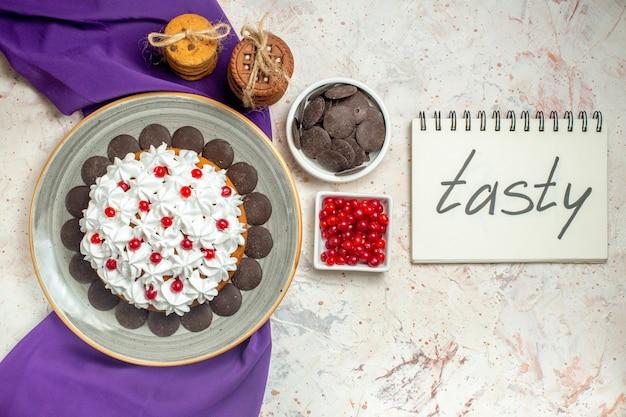 Vista superior do bolo com creme de confeiteiro em prato oval xale roxo biscoitos amarrados com corda de chocolate e frutas em tigelas saborosas escritas no caderno