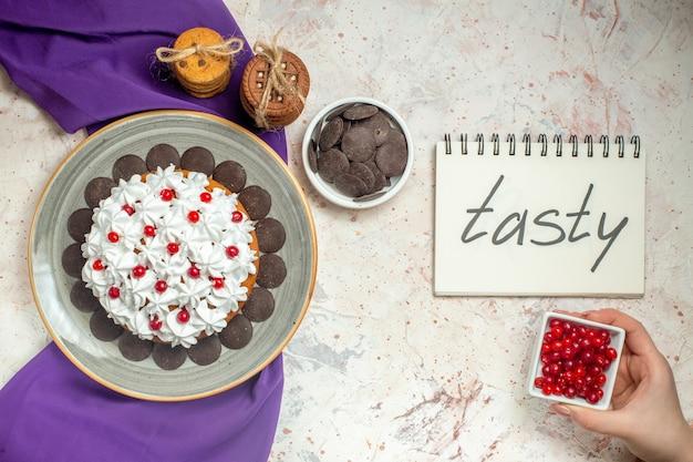 Vista superior do bolo com creme de confeiteiro em prato oval xale roxo biscoitos amarrados com corda tigela de chocolate saboroso escrito no caderno