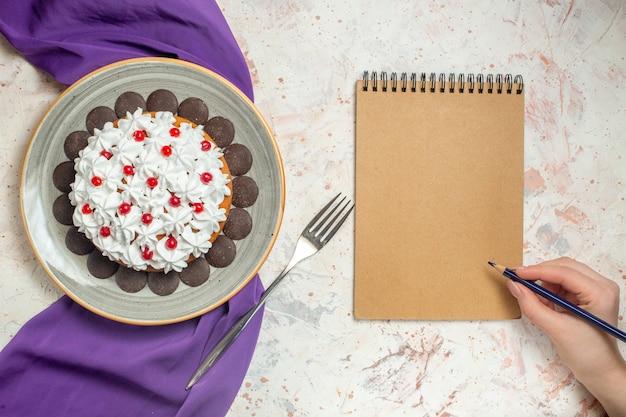 Vista superior do bolo com creme de confeiteiro no prato xale roxo garfo bloco de notas lápis na mão feminina