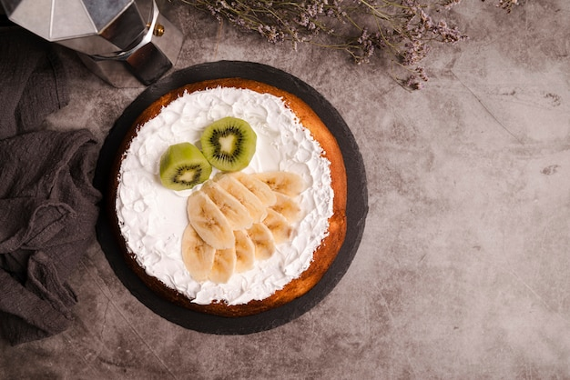 Vista superior do bolo com fatias de kiwi e banana
