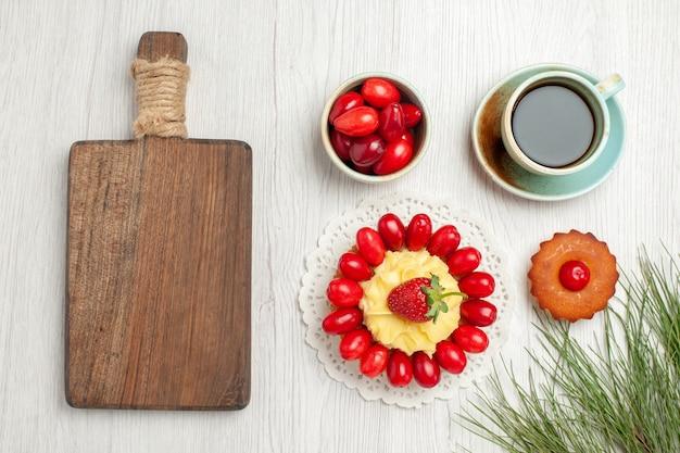 Vista superior do bolo com frutas e xícara de chá na mesa branca