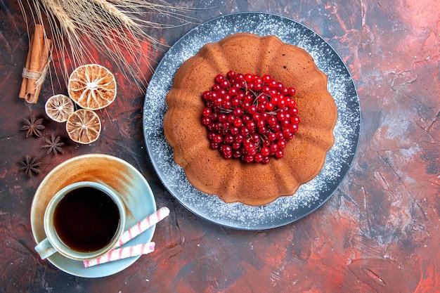 Vista superior do bolo com frutas, uma xícara de chá, limão, canela, bolo com groselha
