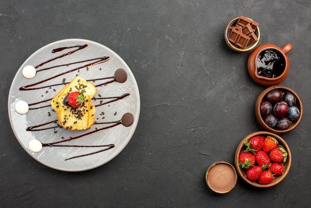 Vista superior do bolo com morango e morango com chocolate em tigelas e prato de bolo com calda de chocolate na superfície escura
