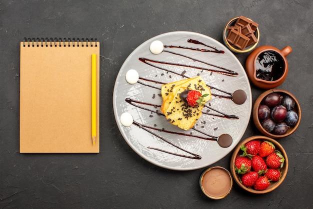 Vista superior do bolo com morango, morango, chocolate e frutas vermelhas em tigelas e prato de bolo com morangos e calda de chocolate ao lado do caderno e lápis na mesa