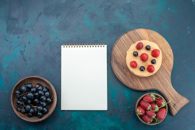 Vista superior do bolo com morangos frescos na superfície azul escura