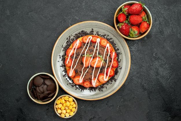 Vista superior do bolo com taças de chocolate de avelã de morango e chocolate ao redor do prato de bolo com chocolate e morango na mesa escura