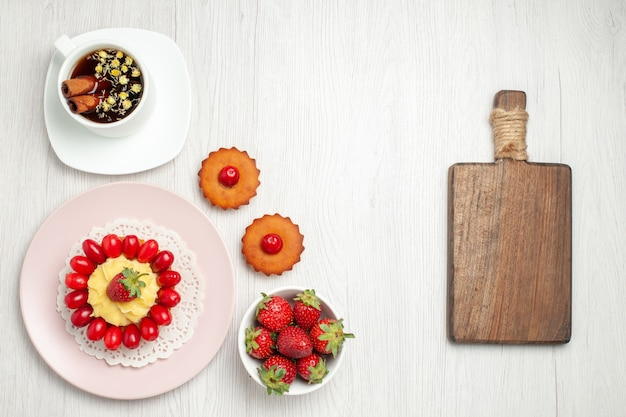 Vista superior do bolo cremoso com frutas e chá em uma mesa branca