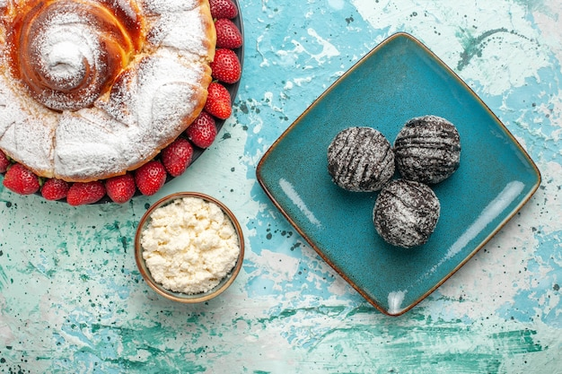 Vista superior do bolo de açúcar em pó com morangos frescos e bolos de chocolate na superfície azul