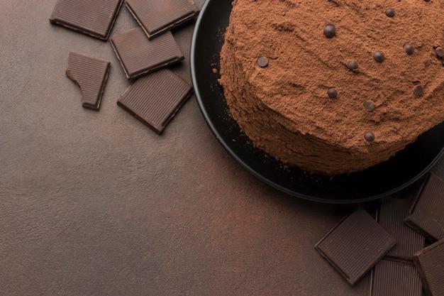 Vista superior do bolo de chocolate com cacau em pó e espaço de cópia
