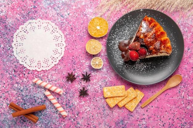 Vista superior do bolo de chocolate com morango e batatas fritas na superfície rosa