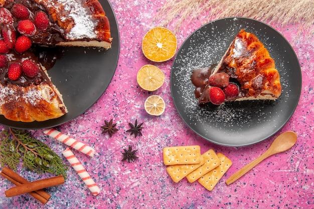 Vista superior do bolo de chocolate com morango e biscoitos na superfície rosa