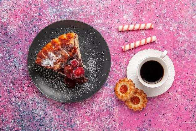 Vista superior do bolo de chocolate de morango com uma xícara de chá e na mesa rosa