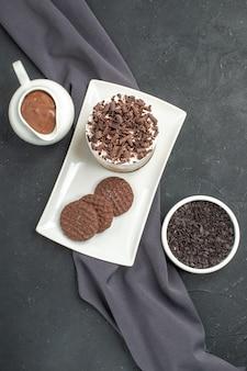 Vista superior do bolo de chocolate e biscoitos em tigelas de prato retangular branco com xale chocolate roxo em fundo escuro isolado