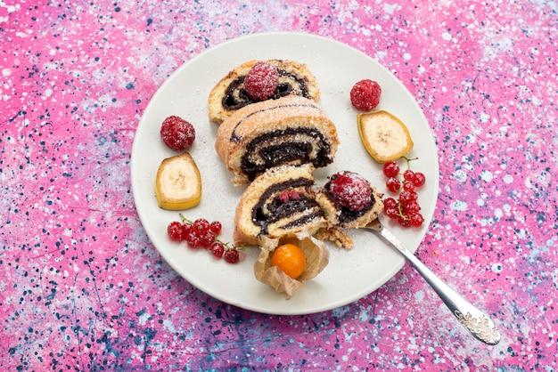 Vista superior do bolo de chocolate em um prato branco com frutas no fundo roxo foto colorida de biscoito doce