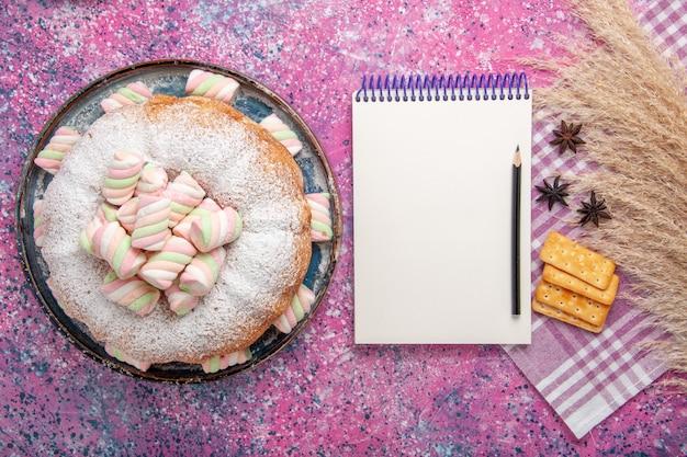 Vista superior do bolo de confeiteiro com biscoitos e bloco de notas na superfície rosa