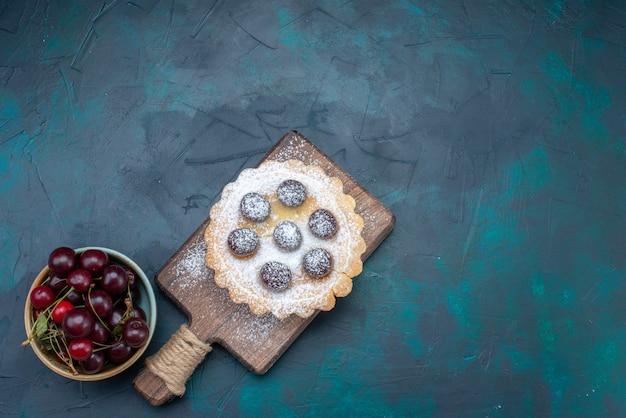 Vista superior do bolo de confeiteiro com cerejas ácidas no fundo azul escuro bolo de açúcar doce fruta foto colorida