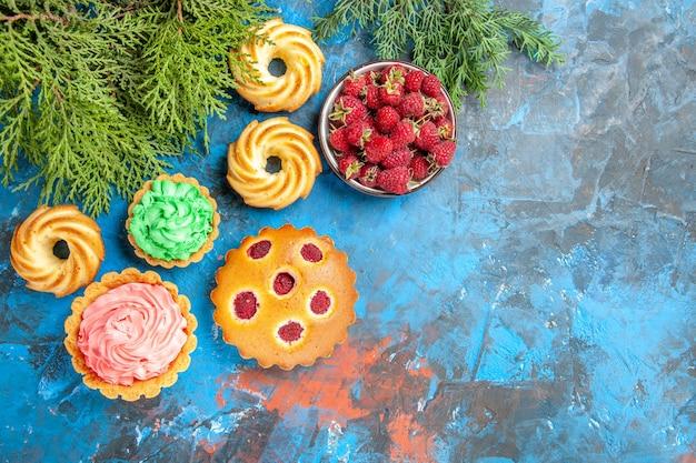 Vista superior do bolo de framboesa, tortinhas pequenas, biscoitos e tigela com frutas na superfície azul