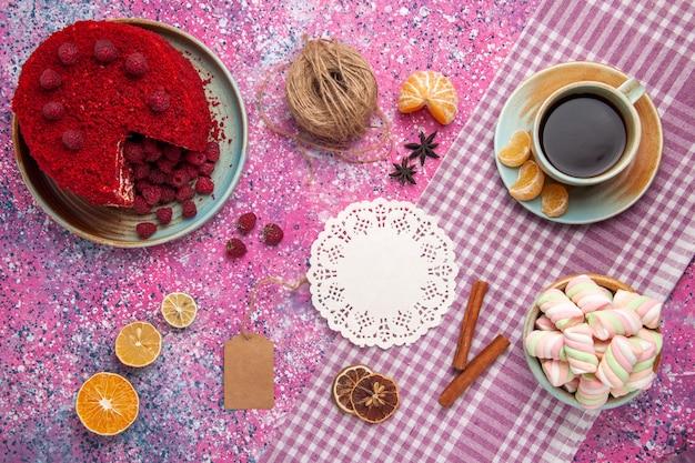 Vista superior do bolo de framboesa vermelha com tangerinas de canela e chá na superfície rosa