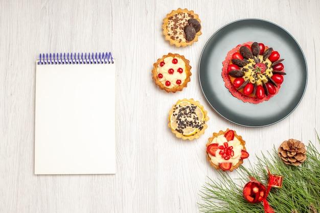 Vista superior do bolo de frutas vermelhas em um prato cinza e tortas no canto superior direito e as folhas do pinheiro no canto inferior direito e um caderno no lado esquerdo do fundo de madeira branco