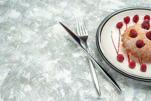 Vista superior do bolo de frutas vermelhas em um prato oval branco cruzado com garfo e faca de jantar em um espaço livre de superfície cinza