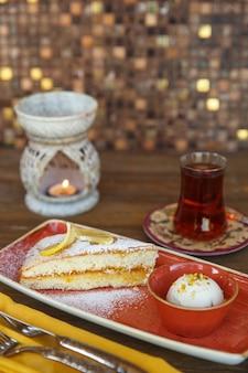 Vista superior do bolo de limão com sorvete de baunilha, servido com chá