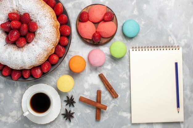 Vista superior do bolo de morango com açúcar em pó e macarons em branco