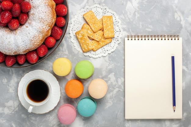 Vista superior do bolo de morango com chá de morangos frescos e macarons em branco