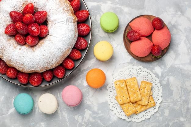 Vista superior do bolo de morango com morangos frescos e macarons em branco claro