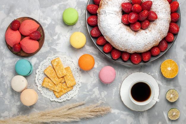 Vista superior do bolo de morango com morangos frescos e macarons em branco
