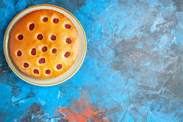 Vista superior do bolo de morango em prato oval na superfície azul