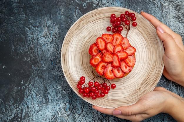 Vista superior do bolo de morango gostoso com frutas vermelhas na mesa escura