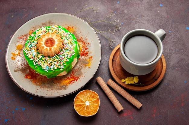 Vista superior do bolo delicioso com biscoito e xícara de chá na superfície escura