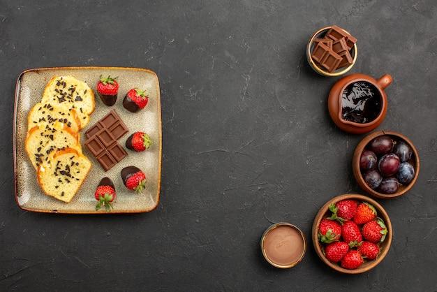 Vista superior do bolo e pedaços de bolo de morangos com chocolate à esquerda e tigelas com morangos, morangos e calda de chocolate à direita da mesa