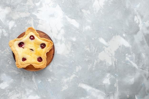 Vista superior do bolo em forma de estrela com cerejas assadas na mesa de luz bolo assar frutas açúcar doce