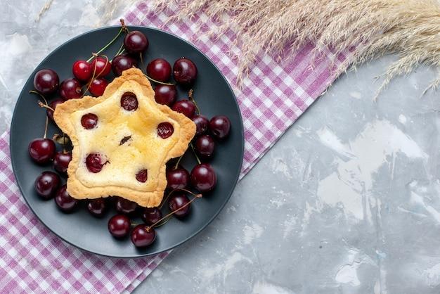 Vista superior do bolo em forma de estrela com cerejas frescas azedas dentro do prato no fundo claro bolo de frutas leve ao forno