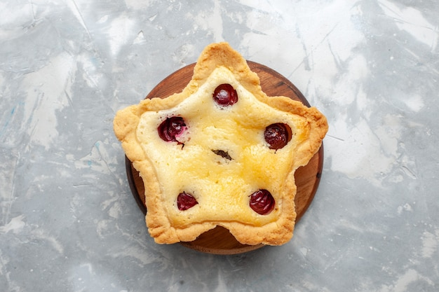 Vista superior do bolo em forma de estrela com cerejas no interior na mesa de luz