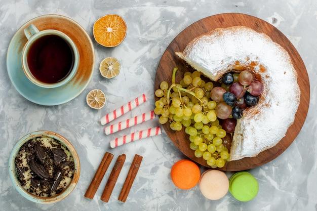 Vista superior do bolo em pó com uvas frescas, canela e macarons na superfície branca