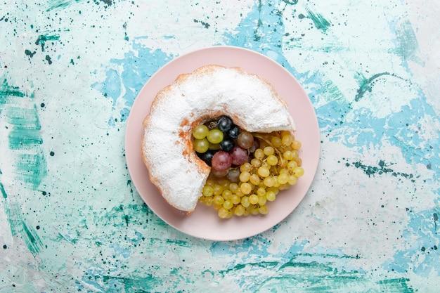 Vista superior do bolo em pó fatiado delicioso com uvas frescas em uma superfície azul clara