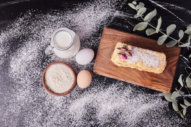Vista superior do bolo napoleão ao lado de ovos, farinha e leite em fundo preto.