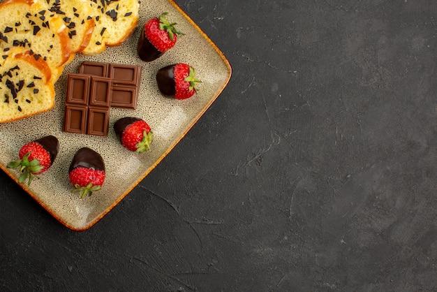 Vista superior do bolo no prato saboroso bolo com morangos cobertos de chocolate e chocolate no prato quadrado cinza no lado esquerdo da mesa