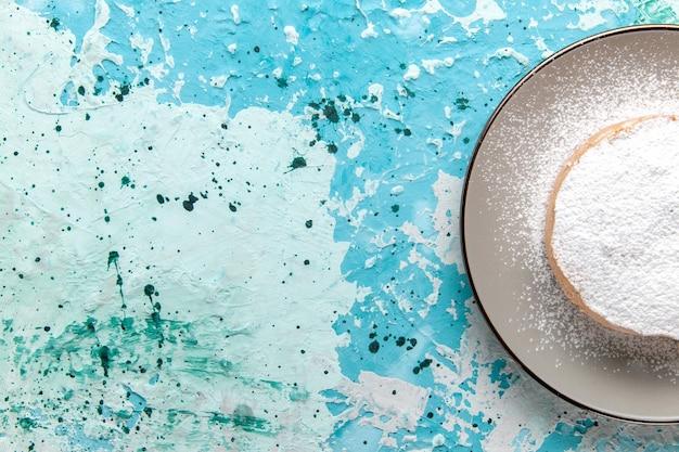 Vista superior do bolo redondo com açúcar em pó dentro do prato na superfície azul clara