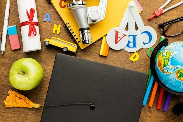 Vista superior do boné acadêmico com material escolar e maçã