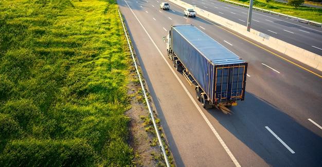Vista superior do borrão de movimento de caminhão branco na estrada rodoviária com recipiente, conceito de transporte.