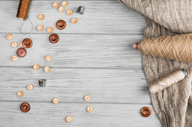 Vista superior do botão; carretel de corda; agulha; dedal e pano em fundo de madeira