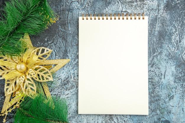 Vista superior do brinquedo da árvore de natal um caderno na superfície cinza
