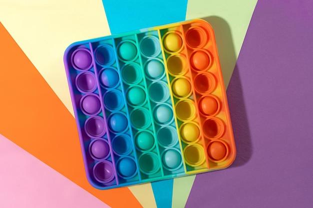 Vista superior do brinquedo sensorial destacando-o no fundo multicolorido cor do arco-íris